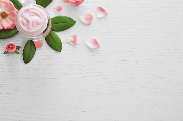 Crème pour le visage et fleurs roses sur bois blanc