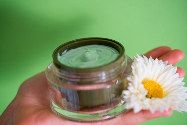Crème pour le visage, pomme verte, marguerite jaune sur fond clair. cosmétiques naturels