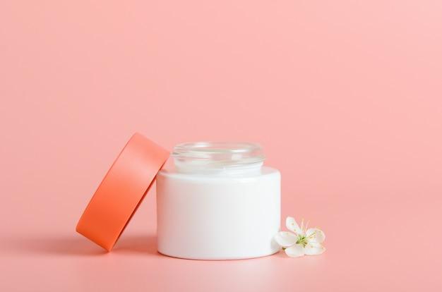 Crème pour le visage en pot blanc avec un couvercle rouge sur fond corail. cosmétiques, beauté. composition minimale.
