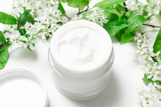 Crème pour le visage en pot sur tableau blanc avec cerisier des oiseaux