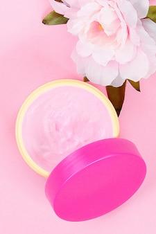 Une crème de soin dans un pot sur un fond pastel avec de belles pivoines. crème anti-âge.