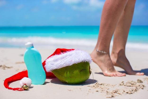 Crème solaire, bonnet de noel sur noix de coco et jambes féminines bronzées sur la plage blanche