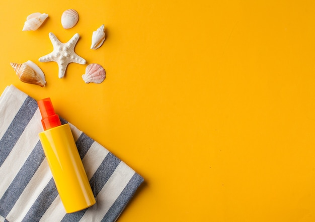 Crème solaire de coquillages d'été sur l'espace de copie jaune