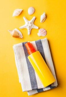 Crème solaire de coquillages d'été sur jaune