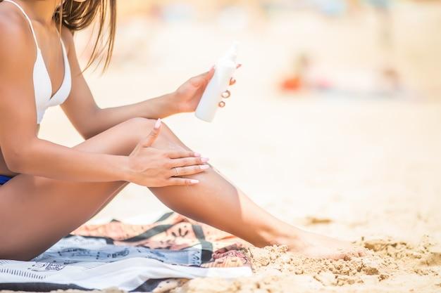 Crème solaire crème solaire en flacon pulvérisateur. jeune femme en pulvérisant de l'huile de bronzage sur sa jambe de bouteille. lady masse une crème solaire tout en prenant un bain de soleil à la plage. modèle féminin pendant les vacances d'été.