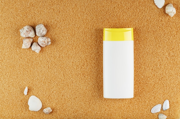 Crème solaire dans une bouteille blanche sur le sable doré avec des coquillages