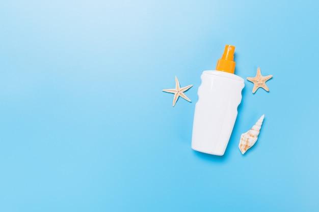 Crème solaire avec étoiles de mer et coquillages en bouteilles sur fond bleu, vue de dessus