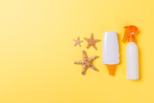 Crème solaire avec étoiles de mer et coquillages en bouteilles sur fond jaune, vue de dessus