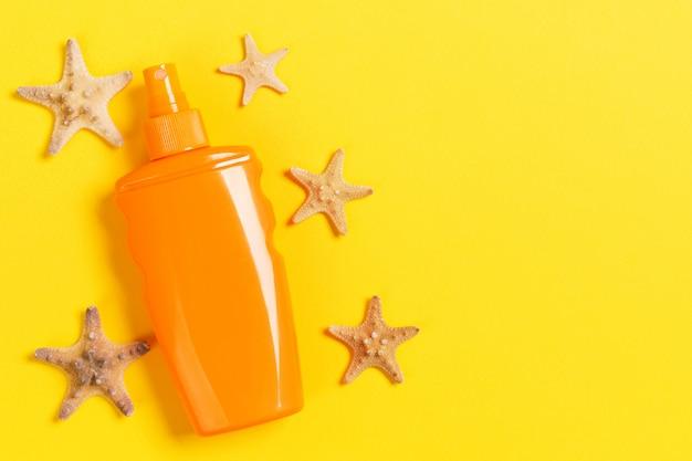 Crème solaire avec des étoiles de mer et des coquillages en bouteilles vue de dessus