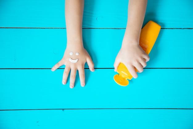 Crème solaire sur la main d'un enfant. mise au point sélective.