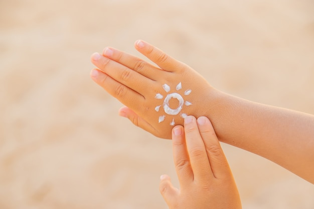 Crème solaire sur la peau d'un enfant. mise au point sélective. la nature.