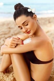 Crême solaire. soins de la peau et du corps. femme en bikini appliquant un écran solaire solaire sur l'épaule bronzée.