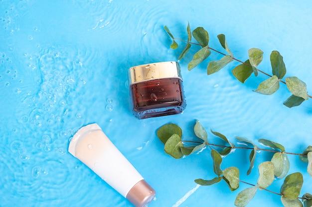 Crème solaire spf lotion pour la peau avec des feuilles d'eucalyptus sur la piscine d'eau bleue