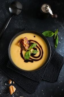 Crème de soupe de pommes de terre au bacon et sauce soja dans un bol noir, sur une surface de béton ancienne sombre