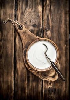 Crème sure fraîche avec une cuillère dans un bol sur une table en bois