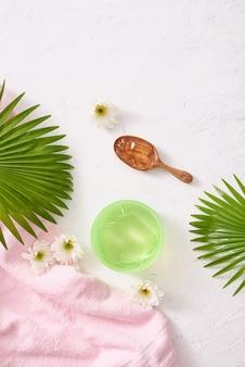 Crèmes cosmétiques avec des feuilles sur fond de table en bois blanc