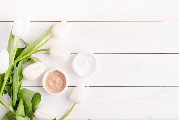 Crèmes cosmétiques avec vue de dessus de tulipes blanches à plat sur fond en bois blanc.