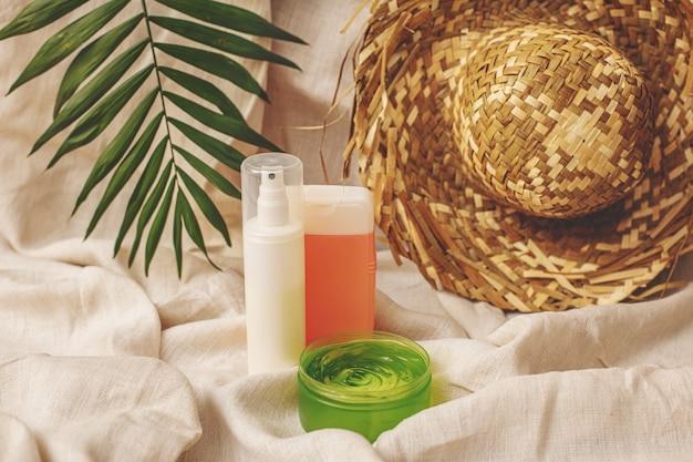 Crèmes et gels cosmétiques d'été avec un chapeau et une feuille de palmier sur fond de tissu en lin