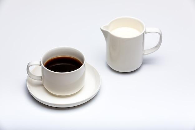 Crémier au lait et tasse de café sur fond blanc