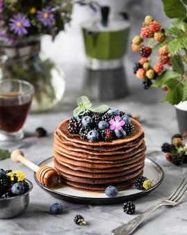 Crêpe au chocolat avec des baies et des fruits avec du miel, avec du sucre en poudre volant et un bouquet de fleurs sauvages sur la table. foncé