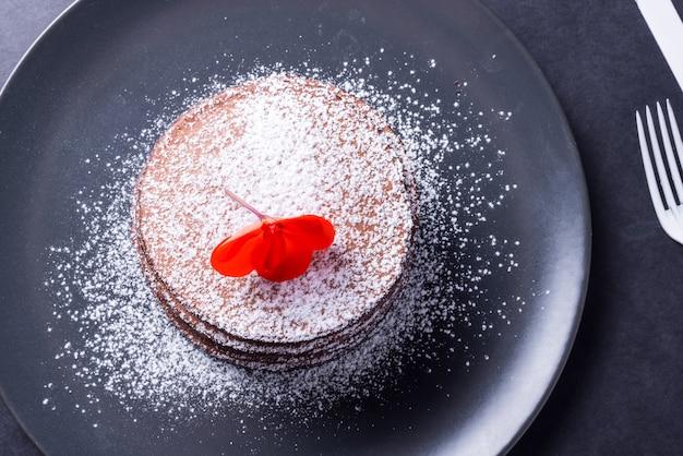 Crêpe au chocolat avec de la poudre blanche et une fleur rouge sur le dessus sur un plat sombre