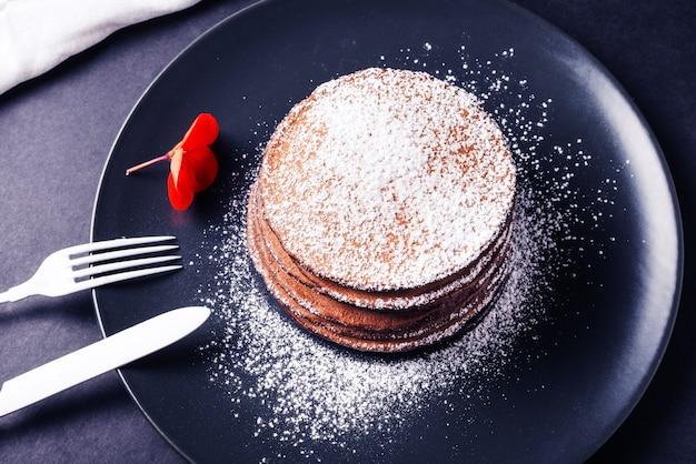 Crêpe au chocolat avec de la poudre blanche et une fleur rouge sur un plat sombre