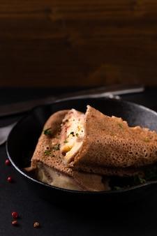 Crêpe au jambon et au fromage fait maison dans une poêle en fer sur fond ardoise noire