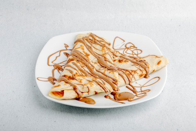Crêpe au sirop de cacao au chocolat dans une assiette blanche sur un fond blanc.