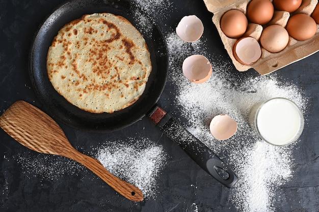 Crêpe chaude dans une poêle noire sur une table noire avec de la farine, du lait et des œufs.