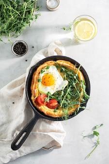 Crêpe hollandaise aux œufs et tomates dans une casserole en fonte sur un tableau blanc