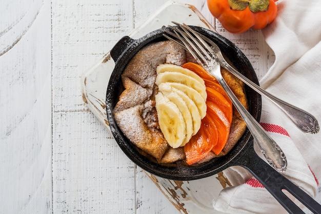 Crêpe hollandaise bébé avec pomme, kaki, banane, cannelle dans une petite casserole en fer sur la surface de la table en bois. vue de dessus.