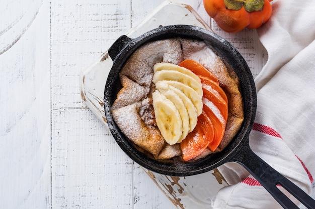 Crêpe hollandaise bébé avec pomme, kaki, banane, cannelle dans une petite casserole en fer sur la surface de la table en bois