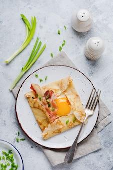 Crêpe avec œuf au plat, fromage, bacon et oignons verts pour le petit déjeuner sur une surface de béton gris clair