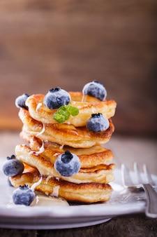 Crêpe pliée pile de miel liquide et bleuets frais