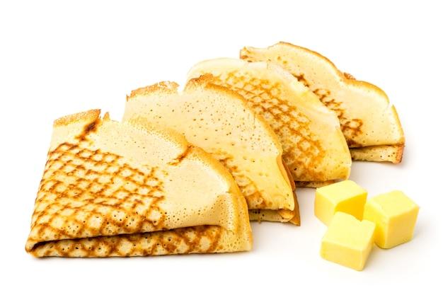Une crêpe pliée en triangle et beurre sur une surface blanche, isolée