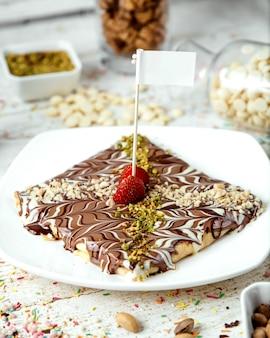 Crêpe recouverte de sirop de chocolat et saupoudrer de pistaches râpées