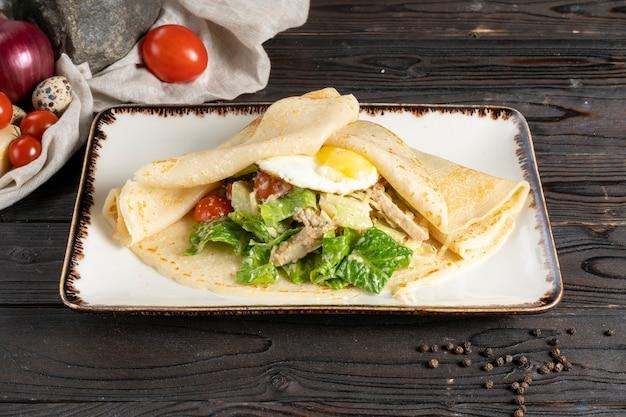 Crêpe avec salade et œuf. plat principal chaud pour le petit-déjeuner ou le déjeuner de crêpes avec œuf au plat, filet de poulet, légumes et salade