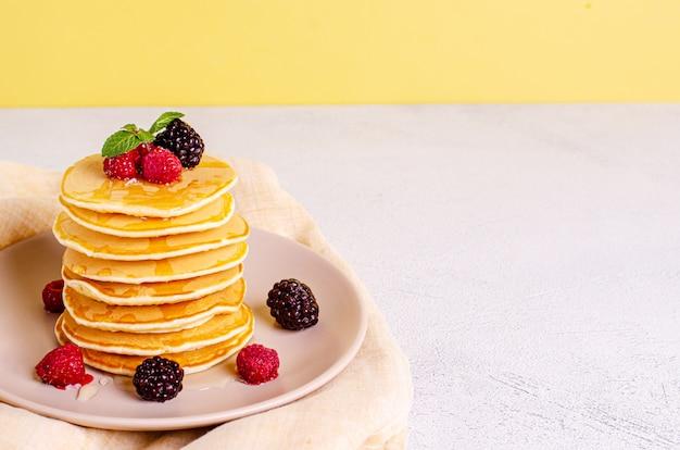 Crêpes américaines classiques faites maison avec des framboises fraîches, des mûres, du miel et des feuilles de menthe, sur une surface claire