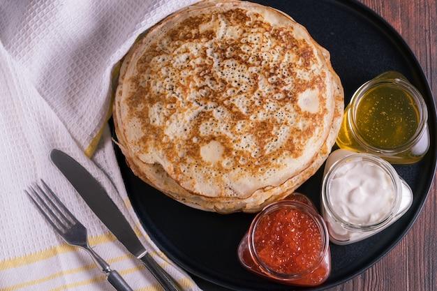 Crêpes sur une assiette avec caviar rouge, miel et crème.