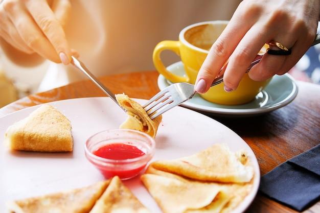 Crêpes avec assiette de confiture de baies. fourchette et couteau dans les mains d'une femme.