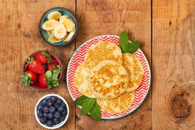 Crêpes sur une assiette rouge et fruits dans des bols sur une table en bois en vue de dessus