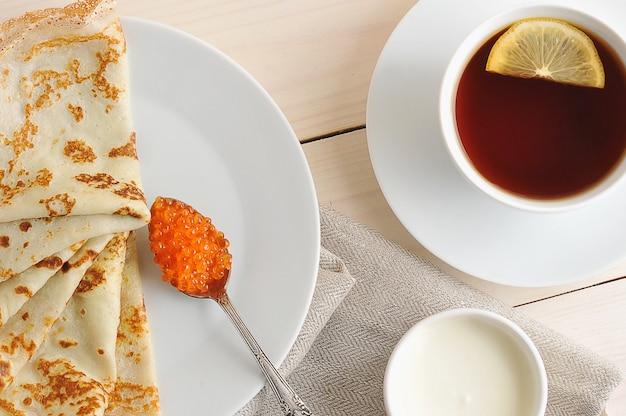 Crêpes au caviar et à la crème sure sur une soucoupe