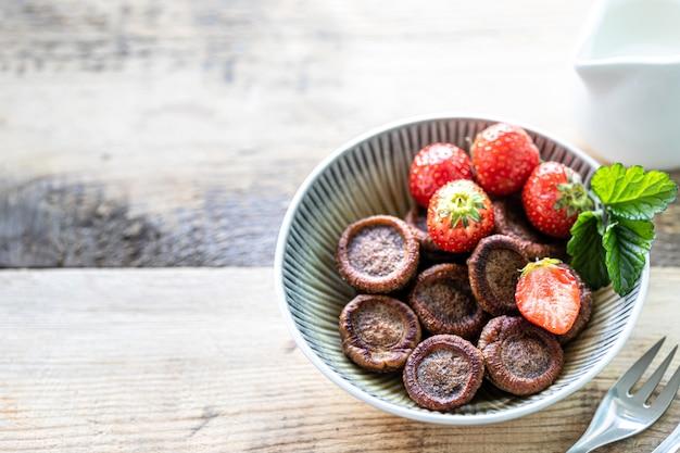 Crêpes au chocolat minuscules dans un bol avec des fraises et de la crème