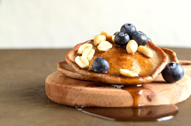 Crêpes au chocolat avec des myrtilles sur un fond sombre.