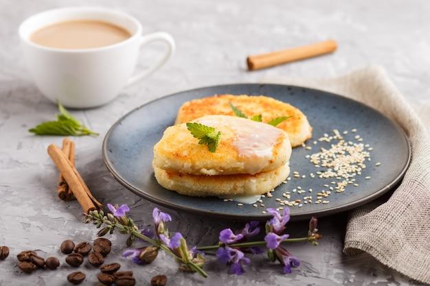 Crêpes au fromage sur une assiette en céramique bleue et une tasse de café sur du béton gris