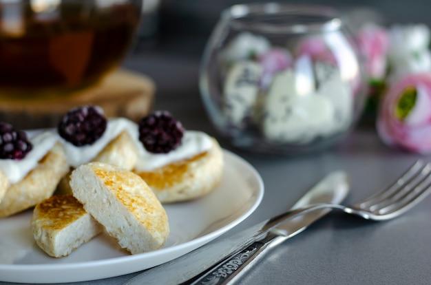 Crêpes au fromage blanc avec crème sure et mûres au petit déjeuner.