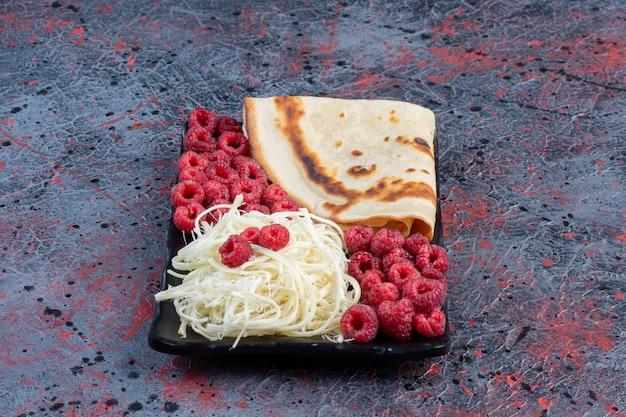 Crêpes au fromage blanc et framboises dans une assiette blanche.