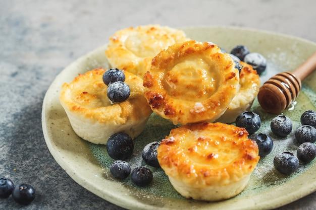 Crêpes au fromage cottage aux bleuets et au miel, fond gris. concept de cuisine russe.