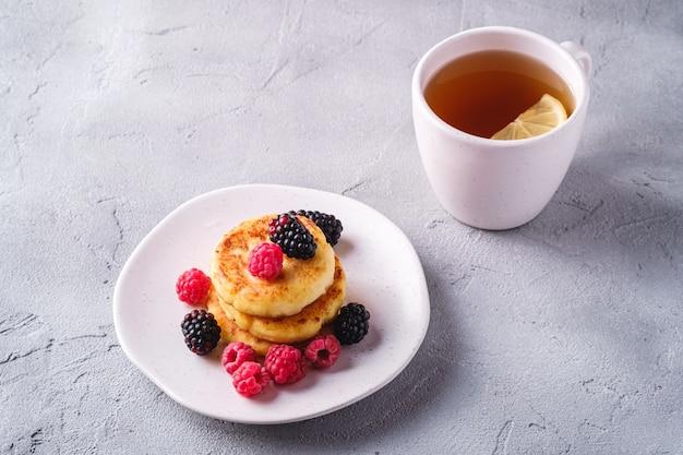 Crêpes au fromage cottage avec des baies dans une assiette près d'une tasse de thé chaud avec une tranche de citron