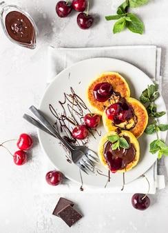 Crêpes au fromage cottage ou beignets au chocolat et à la confiture de cerises, à la cerise fraîche et à la menthe. cuisine traditionnelle ukrainienne et russe. petit déjeuner sain et diététique.